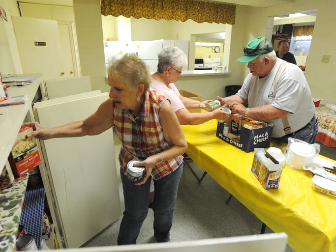 Ruby Reed, left, Susan Reed and John Reed fill a box at Love Thy Neighbor food pantry at Iliff United Methodist Church. The food pantry is open on Mondays, serving those in need in the Crooksville area.