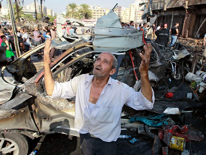 A man prays at the scene of a car bomb attack outside the Al-Taqwa Mosque on Aug. 23 in Tripoli, Lebanon. Two car bombs killed dozens of people as tension rose between Lebanese supporters and opponents of Syrian President Bashar Assad.