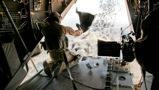A U.S. Marine drops leaflets in Afghanistan in 2011.