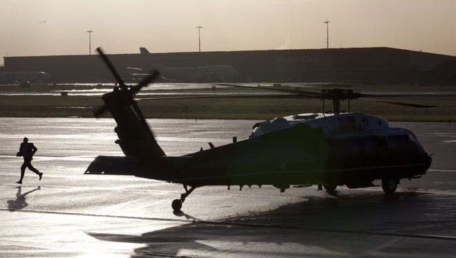 A U.S. Secret Service agent runs past Marine One on the tarmac before the arrival of President Obama at Schiphol Amsterdam Airport.