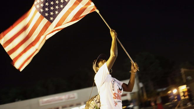 A demonstrator protesting the shooting of Michael Brown waves the American flag Aug. 21 in Ferguson, Mo.