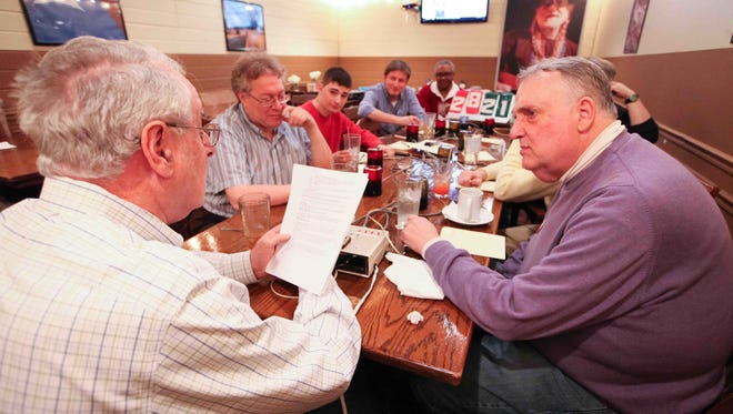 Joel Lipman (left) reads out a question as trivia masters from around the area who have appeared on TV, won at national events and written books, gather at Lone Star Steakhouse & Saloon to test each other on questions they wrote.