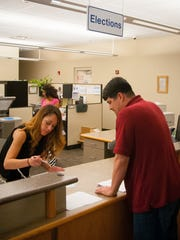Document Technician Laura Rosales helps Steve Calderazzo obtain a copy of his voter registration at the County Clerk's Office on Tuesday. The office has begun implementing new steps to safeguard its voter rolls in the wake of an identity theft and check cashing scandal at the office revealed in June.