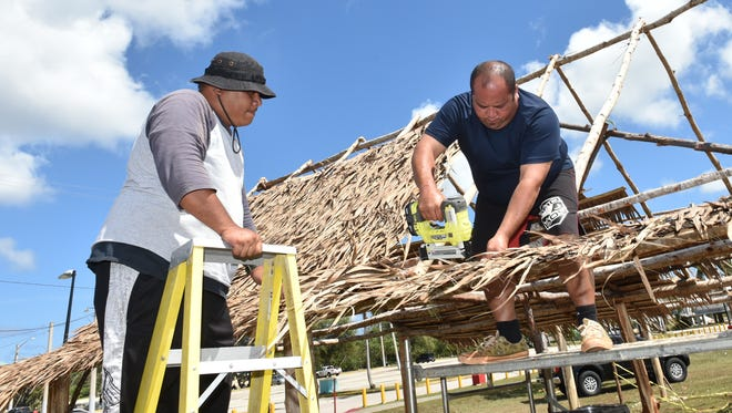 In this file  photo, G Hocog, left, and Nono Calvo, from the Department of Corrections, build a thatch roof for what will be part of the FestPac Information Center at Paseo.