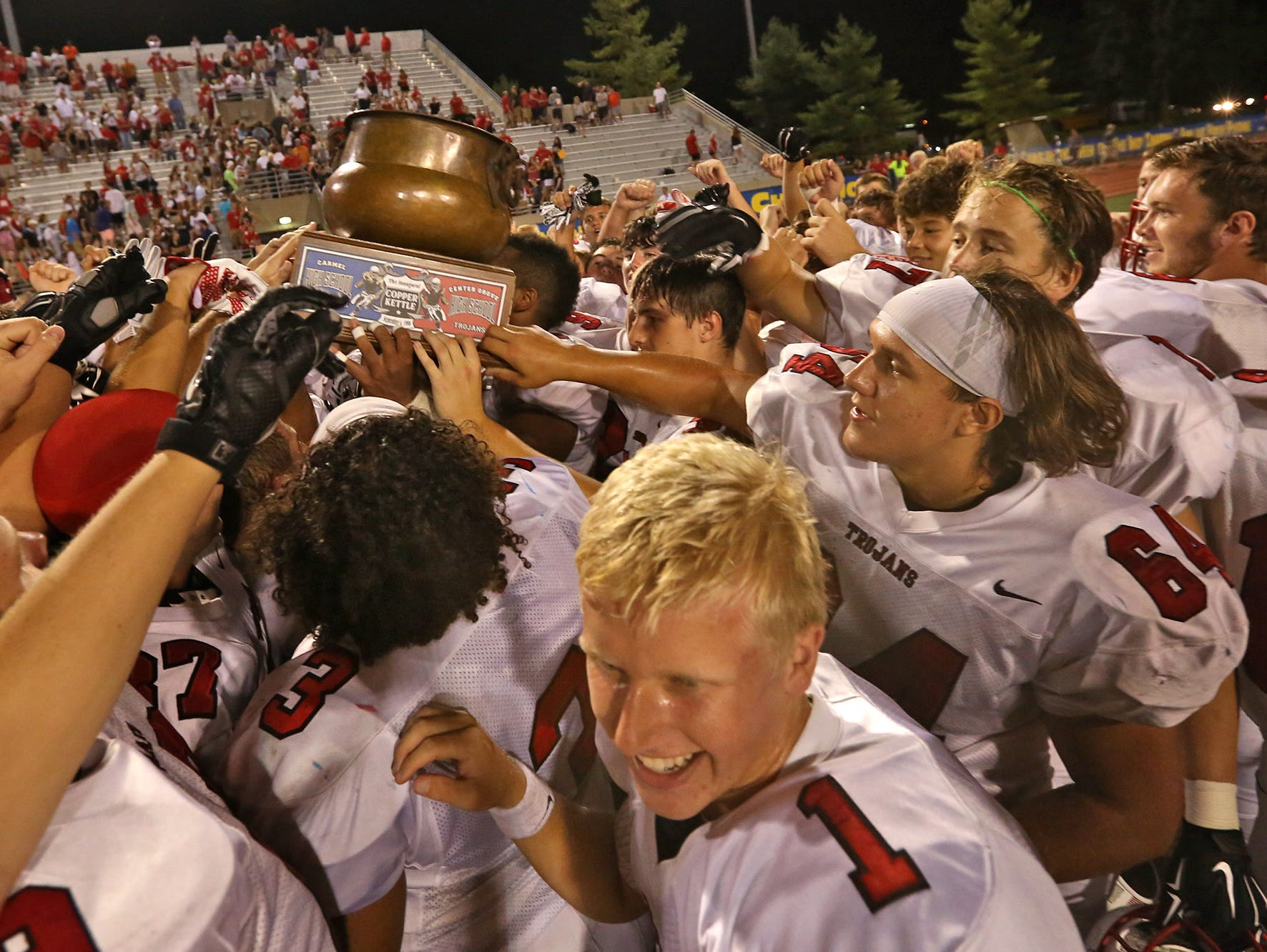 Center Grove teammates hold the Copper Kettle trophy after winning the football game at Carmel High School, Friday, September 4, 2015, 24-21.