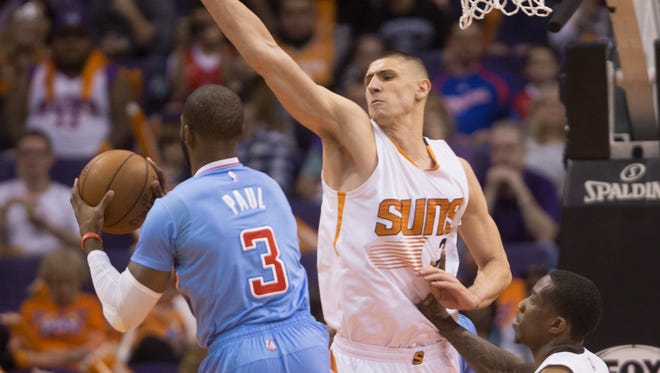 Suns' Alex Len defends Clippers' Chris Paul as he jumps in the lane in the second quarter at US Airways Center in Phoenix, AZ on January 25, 2015.