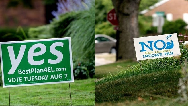 Yard signs urge East Lansing residents to vote both for an against an East Lansing income tax on August 7, 2018. The income tax rate would be 1% for residents and 0.5% for non-residents. Approval of the income tax would trigger a 5-mill reduction in East Lansing property taxes.