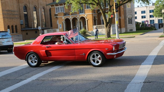 A vintage Ford Mustang displays the American flag while participating in in the 2017 Cruisin' the Capitol event in downtown Topeka.
