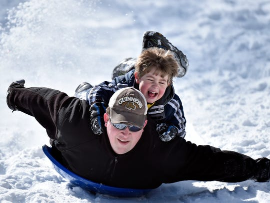Charlie Perkins gets a ride on a snow disc from his father, David, as they speed down a snow-covered street, Tuesday, Feb 17, 2015, in Roanoke, Va. A winter storm blasted parts of the Mid-Atlantic and the South on Tuesday, creating treacherous road conditions and leaving hundreds of thousands without power.
