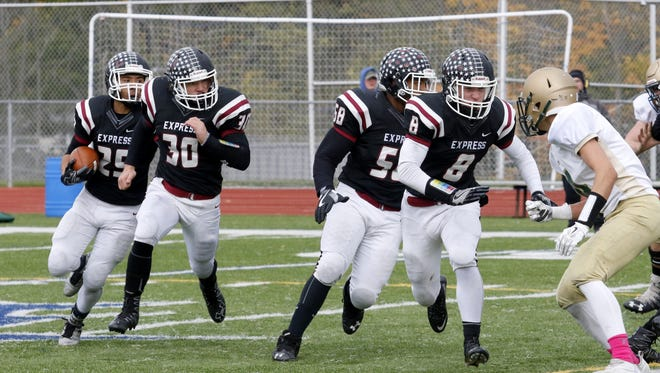 Tim Davis follows the blocking of Charlie Mahon (30), Reece Harriel (58) and Josh Friebis (8) to pick up a first down for Elmira during a 34-22 victory over Vestal on Saturday at Ernie Davis Academy.