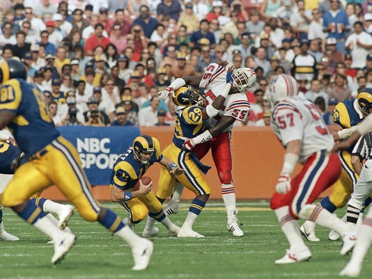 FILE - In this Nov. 16, 1986, file photo, Los Angeles Rams running back Eric Dickerson (29) blocks New England Patriots linebacker Don Blackmon (55) as he protects his quarterback, Jim Everett, left, during the second quarter of an NFL football game in Anahein, Calif. Eric Dickerson is thrilled his Rams have returned to Los Angeles after 21 years away, but the Hall of Fame running back says the current players in the horned helmets must be ready for both the challenges and the opportunities presented by playing in the nation's glitzy entertainment capital. Former Rams quarterback Jim Everett says the Rams must be careful to stay focused on football amid the distractions of Hollywood.(AP Photo/Bob Galbraith, File)