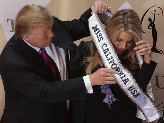 Donald Trump place a sash on Miss California USA, Carrie Prejean following a news conference in New York in 2009.