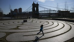A young girl runs the labyrinth at Smale Riverfront