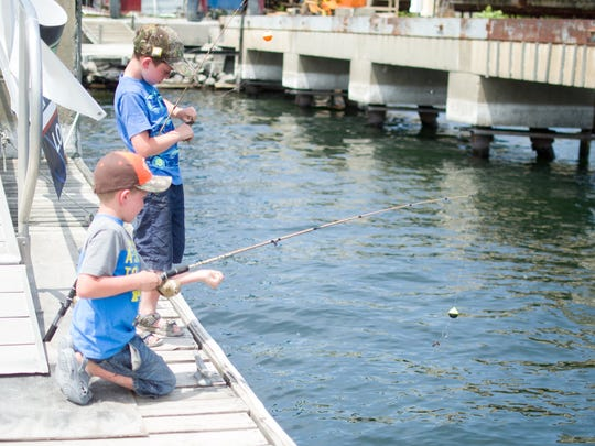 Left, Hunter Bleau, 8, and Cameron Bleau, 9, brothers from Fairfax fish on the docks of the Shelburne Shipyard during the annual Lake Champlain International Father's Day fishing derby on Sunday.