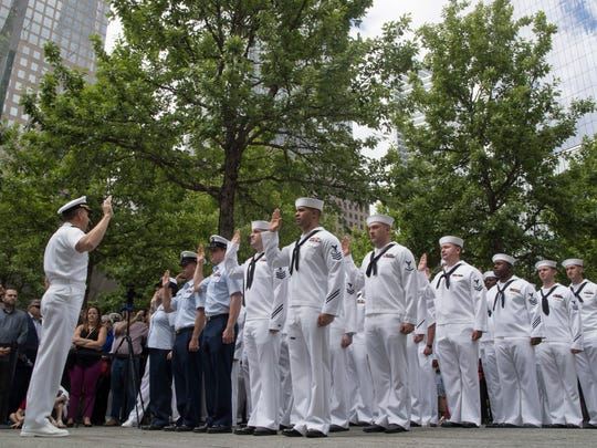 Adm. Phil Davidson, left, commander of the U.S. Fleet Forces Command/Naval Forces U.S. Northern Command, administers the Oath of Reenlistment to U.S. Navy, and U.S. Coast Guard service members at the National September 11 Memorial on Friday.