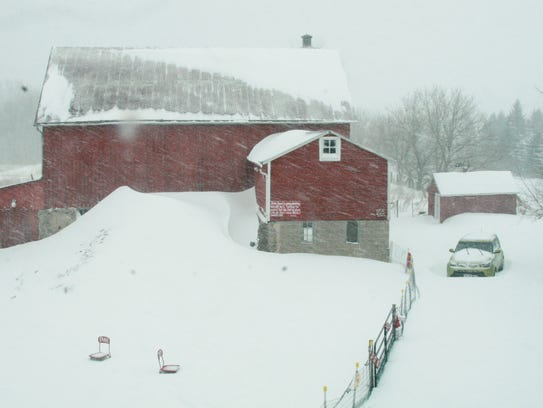 Snow piles up Sunday on a farm north of Appleton. Snow is expected to continue through Sunday with record-breaking totals in northeastern Wisconsin.
