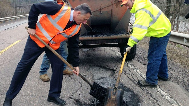 Vermont Gov. Peter Shumlin, left, assists a pothole crew patching U.S. 2 on May 3 in Middlesex.