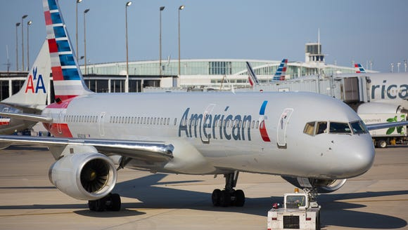 Crews push an American Airlines Boeing 757 out of the