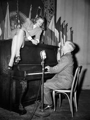 FILE - In this Feb. 10, 1945 file photo, Vice President Harry S. Truman plays the piano as actress Lauren Bacall lies on top of it during her appearance at the National Press Club canteen in Washington. Bacall, the sultry-voiced actress and Humphrey Bogart?s partner off and on the screen, died Tuesday, Aug. 12, 2014 in New York. She was 89. (AP Photo, File)