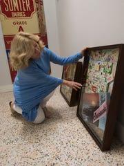 Brew Ha Ha owner Angela Thames Walker hangs Pensacola-themed memorabilia inside her new restaurant Feb. 26, 2018.
