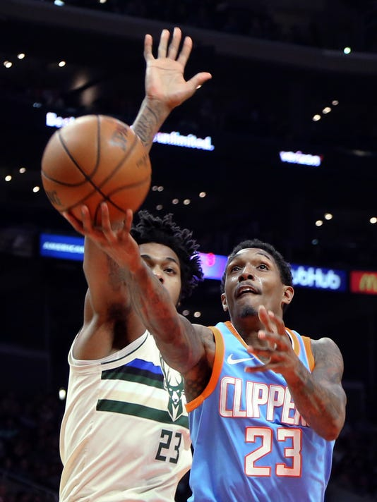 Los Angeles Clippers guard Lou Williams (23) shoots as Milwaukee Bucks guard Sterling Brown (23) defends during the second half of an NBA basketball game in Los Angeles on Tuesday, March 27, 2018. The Clippers won 105-98. (AP Photo/Reed Saxon)