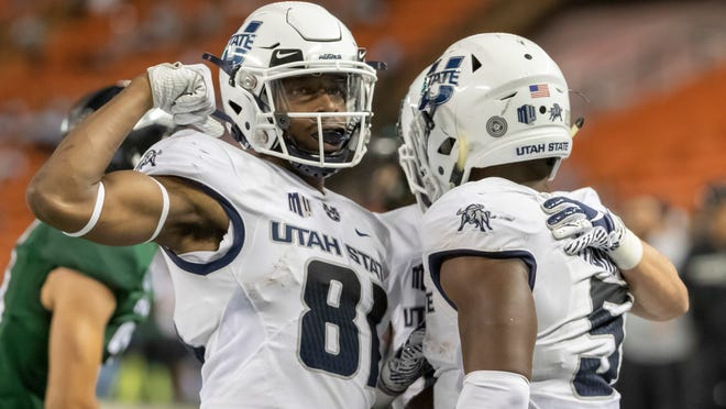 FILE - In this Saturday, Nov. 3, 2018 file photo, Utah State wide receiver Savon Scarver (81) celebrates a touchdown run by his teammate running back Darwin Thompson (5) in the second half of an NCAA college football game against Hawaii in Honolulu. The high-flying offenses of Utah State and North Texas meet in the New Mexico Bowl in what is expected to be a passing attack shootout. Utah State is making its seventh college postseason appearance in eight years while North Texas tries to give head coach Seth Littrell his first bowl victory. (AP Photo/Eugene Tanner, File)