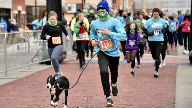Jace Olson and his dog take off at the starting line for the Frost Fun Runs to benefit Big Brothers Big Sisters of Salina in downtown Salina on Saturday morning..