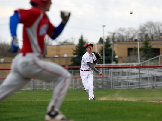 Big Reds' shortstop Ian Abraham makes a throw to first base Monday, April 17, during boys baseball action at Port Huron High School.