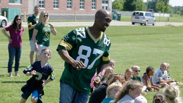 Robert Brooks still has the moves as he plays duck duck goose with some of the YMCA campers at the surprise stop in Oshkosh. The Green Bay Packers Tailgate Tour made a surprise stop at the 20th Avenue YMCA Friday, June 17, 2016.