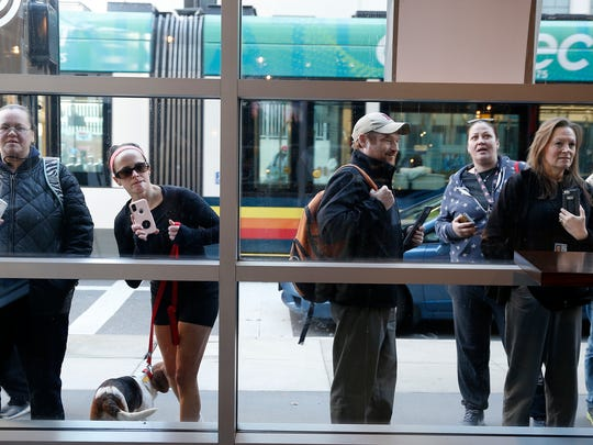 Fans look through the windows of Wahlburgers in Downtown to see the owner Mark Wahlberg Monday February 26, 2018.
