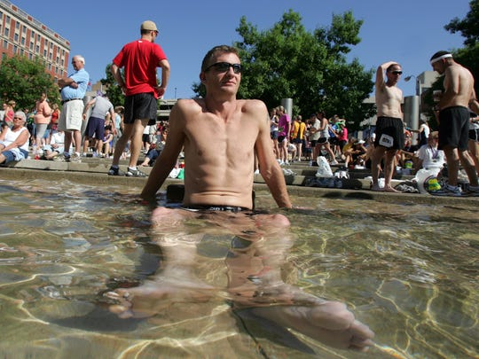 Deon Wingert of Carroll cools off in the wading pool in Nollen Plaza after finishing his run in the 30th Dam to Dam 20K road race in 2009.