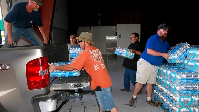 Mike Melott, left, Jason Martinez, center, and Robert McGimsey, right, load up water for their neighbors in Crouch Mesa on June 20, at McGee Park. In back is Mike Mestas with the San Juan County Office of Emergency Management. The water company that supplies that area is under investigation by two state agencies.