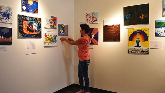 Joan Swenson, with Tallgrass Recovery, puts up artist statements for the Student Recovery Art Show Thursday, May 26, 2016, at Exposure Gallery in downtown Sioux Falls.