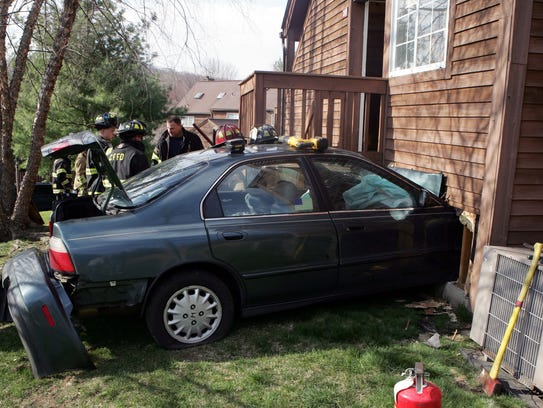 Brewster and Croton Falls firefighters work at the scene of a vehicle into a house at 201 Seven Fields Drive in the Reed Farm section of Southeast April 18, 2009. The driver was transported to Putnam Hospital Center. The occupants of the house were uninjured. (Frank Becerra Jr./The Journal News)
