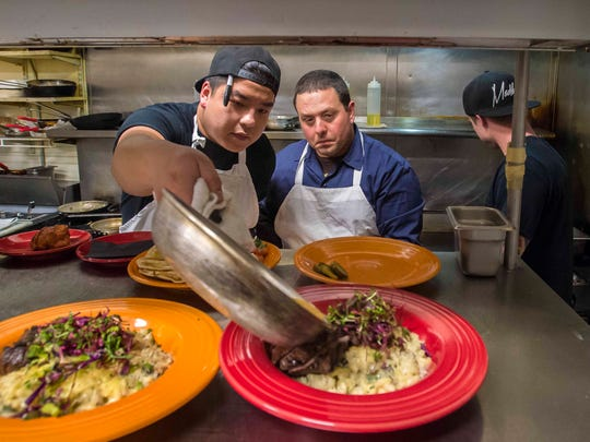 Chef Frank Pace, center, watches as cook Qui Nguyen
