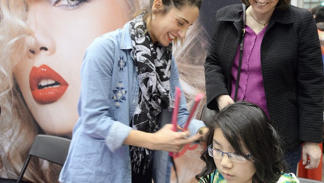 Martha Sabourin, from Williamston, right, smiles as Maya Lasage uses a flat iron on her 11-year-old daughter Jade's hair at 2014 Mid-Michigan Women's Expo at the Lansing Center.