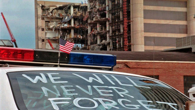 """In this April 24, 1995 file photo, an Oklahoma City police car decorated with the words, """"We will never forget,"""" and a small American flag sits near the Alfred P. Murrah Federal Building in Oklahoma City. The blast killed 168 people -- including 19 children -- injured hundreds more and caused hundreds of millions of dollars in damage to structures and vehicles in the downtown area."""