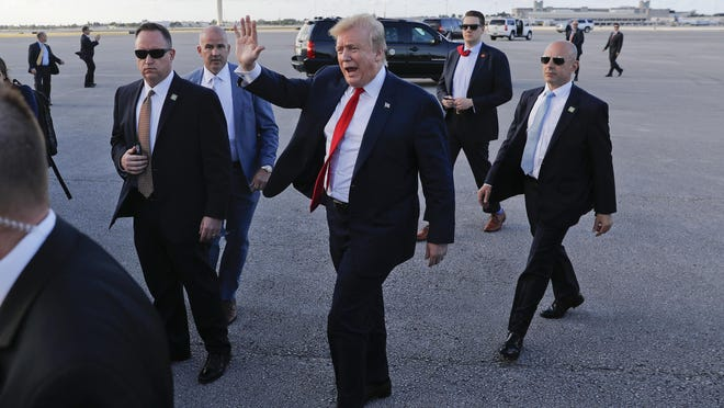 In this April 18, 2019, photo, President Donald Trump, center, surrounded by members of the Secret Service, walks across the tarmac to begin to greet supporters during his arrival at Palm Beach International Airport, Thursday, April 18, 2019, in West Palm Beach, Fla. (AP Photo/Pablo Martinez Monsivais)