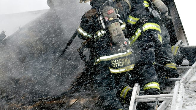Quincy Fire Chief Mike Sherman and two other firefighters tear open a metal roof April 17 at 243 Sanford Road, in a mutual-aid effort with Coldwater Fire Department.