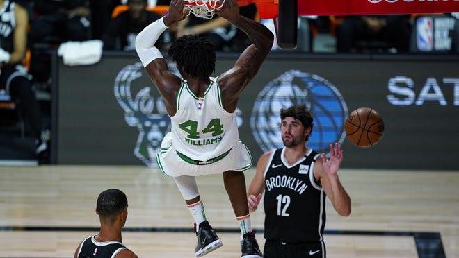 Boston Celtics center Robert Williams III (44) follows through on a dunk over Brooklyn Nets forward Joe Harris (12) during the first half of an NBA basketball game Wednesday, Aug. 5, 2020 in Lake Buena Vista, Fla.