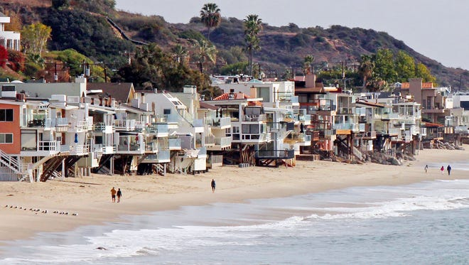 FILE--In this Dec. 20, 2015, file photo, waves roll up to and under homes perched over a sandy beach in Malibu, Calif. The picturesque California beachside city of Malibu has banned  banned single-use plastic straws, stirrers and cutlery. The City Council voted Monday, Feb. 26, 2018, to approve an ordinance prohibiting the sale, distribution and use of the plastic items starting June 1. (AP Photo/John Antczak, file)