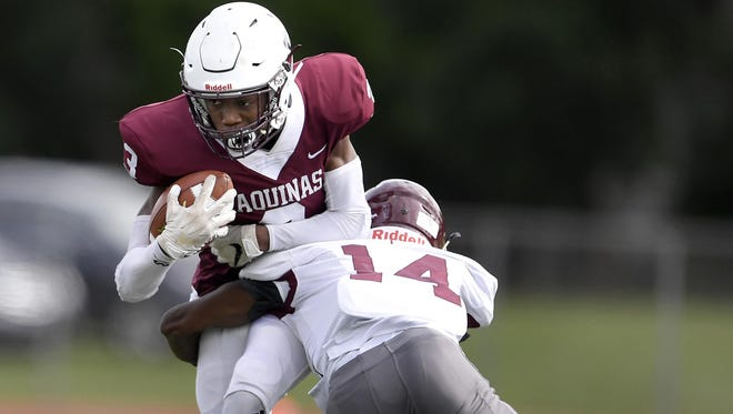 Aquinas' Damon Montgomery, left, is tackled by St. Joseph's Anthony McCarley during a regular season game played at Aquinas Institute on Saturday, Sept. 22, 2018. Aquinas beat St. Joseph's-VI 49-21.