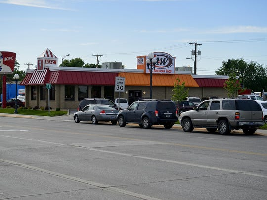 A line of cars for the KFC-A&W drive-thru wait for their turn on Thursday.