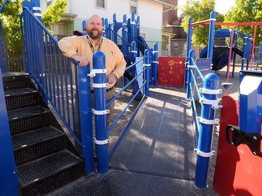 Whittier Elementary School Principal Ryan Hart stands with the school's wheelchair-accessible play structure. The accessibility comes in the form of ramps and wider platforms.