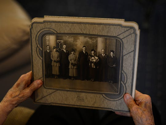 Madeline holds a picture from her wedding day in 1936.