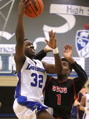La Vergne's Robjhay Bush (32) goes up for a shot as he is guarded by Stewarts Creek's Breyden Jackson (1) during the District 7-AAA boys consolation game on Tuesday, Feb. 23, 2016, at La Vergne.