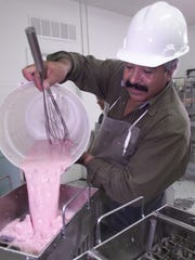 2002: Alfonso Escobedo pour freshly made strawberry cream into a mold at the Fruitiki  plant.