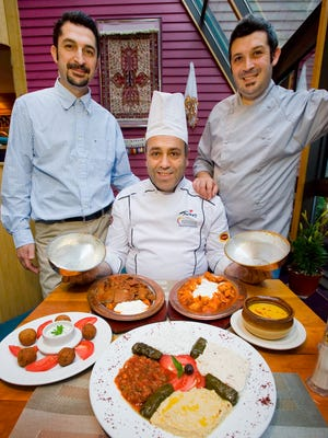 Istanbul Kebab House owner Vural Oktay (left) and his brother Hasan Oktay (right) with their chef Memet Kurtlu and some of their traditional offerings in Essex Junction on June 26, 2012.