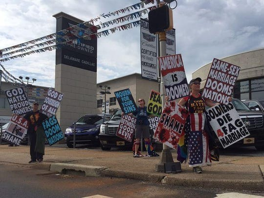 A woman in the center of these Westboro protesters can be seen dragging the flag that is tied to her legs.