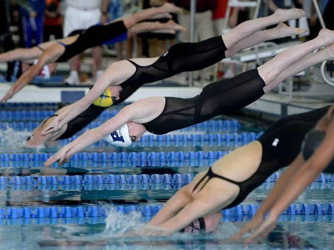 Katie Smith, center with white cap, owns two individual and shares two relay Pittsford girls swimming records.